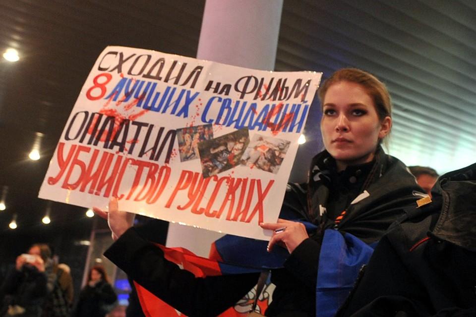 Прямо напротив входа, завернувшись в флаг Новороссии, стояла известная активистка Национального фронта Мария Катасонова