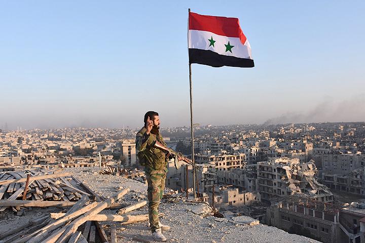 Боец сирийской армии осматривает районы Алеппо, отбитые накануне у боевиков сил оппозиции.