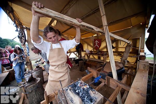 Средневековая кузница. Мастер раздувает огонь с помощью ручного обдува.