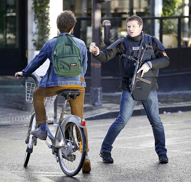 Полицейский пытается остановить парижанина на велосипеде, проезжающего мимо места проишествия. Фото: REUTERS