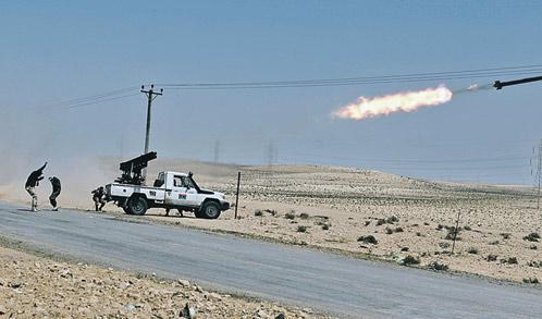 Повстанцы последними снарядами отстреливаются от наступающих правительственных войск. Но силы не равны: оппозиционеры откатываются все дальше на восток. Фото: АП