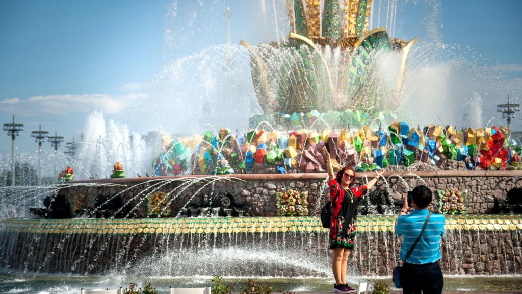 женщина фотографируется на фоне фонтана на вднх