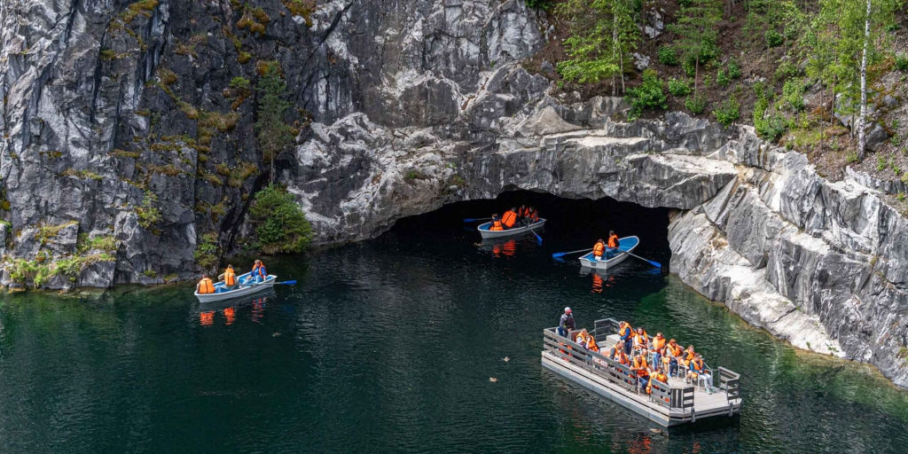 туристы плывут по мраморному озеру