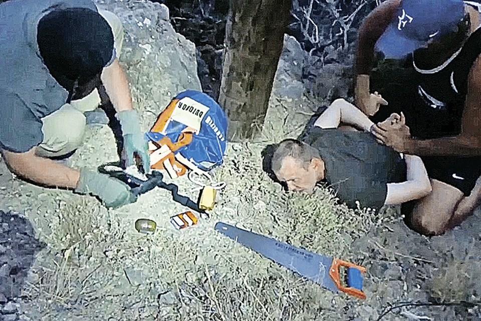 Геннадия Лимешко задержали в тот момент, когда он пилил деревянный столб линии электропередачи. Фото: Оперативная съемка ФСБ РФ