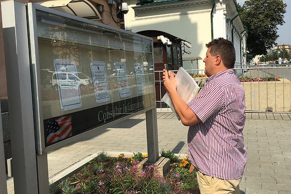 Посетитель фотографирует документы на стенде возле посольства США.