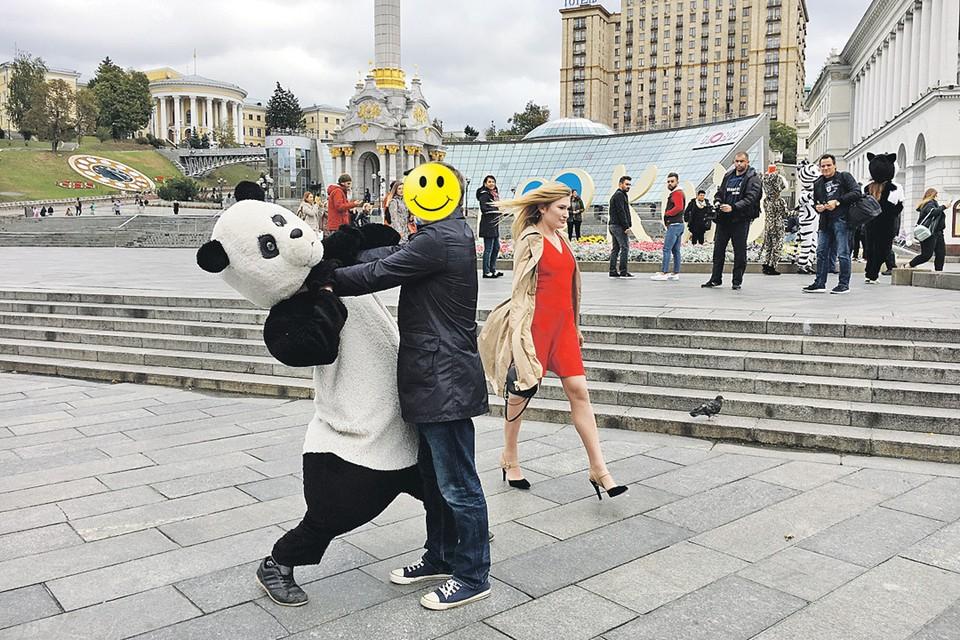 Корреспонденту приходится закрывать лицо, чтобы не было проблем у его друзей и родственников, живущих на Украине. На заднем плане - смуглые брюнеты с интересом разглядывают проходящую мимо блондинку. И таких явно приезжих мужчин в Киеве, по нашим наблюдениям, стало очень много. Фото авторов
