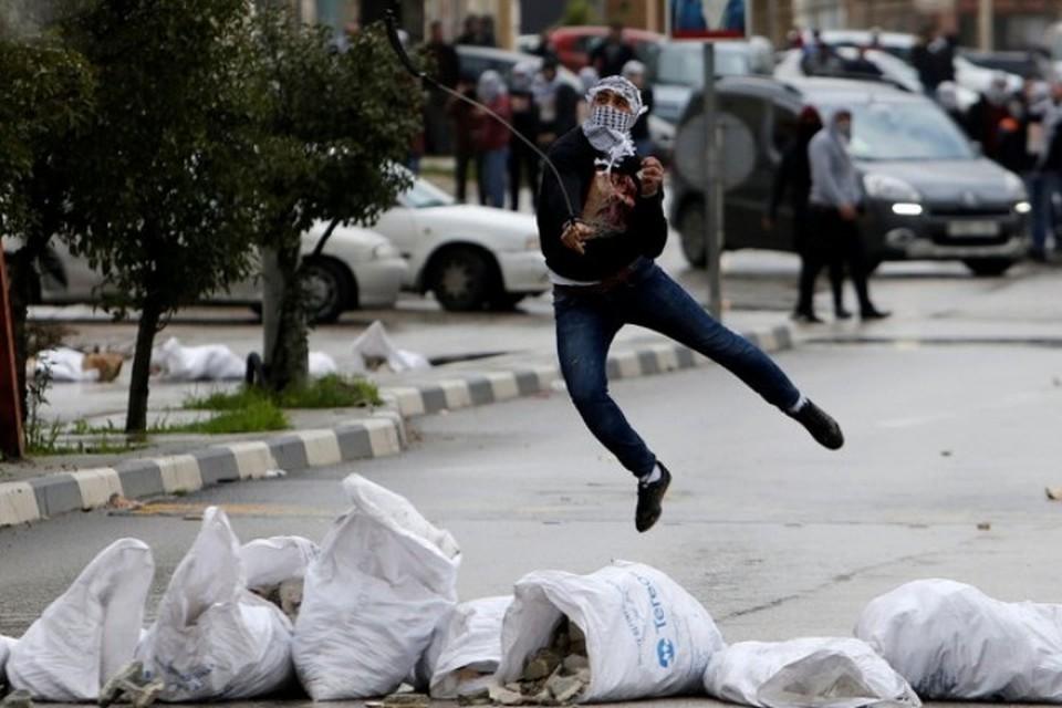 Протестующий палестинец бросает камни в израильских военных