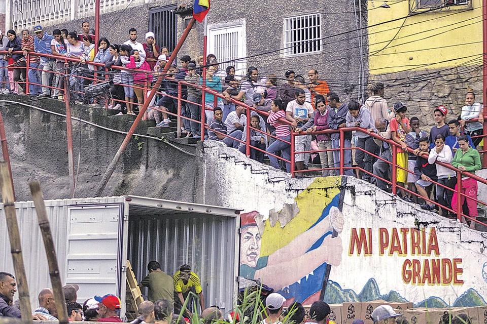 На фоне граффити с изображением экс-президента Уго Чавеса жители Каракаса стоят в очереди за едой, распределяемой правительством.