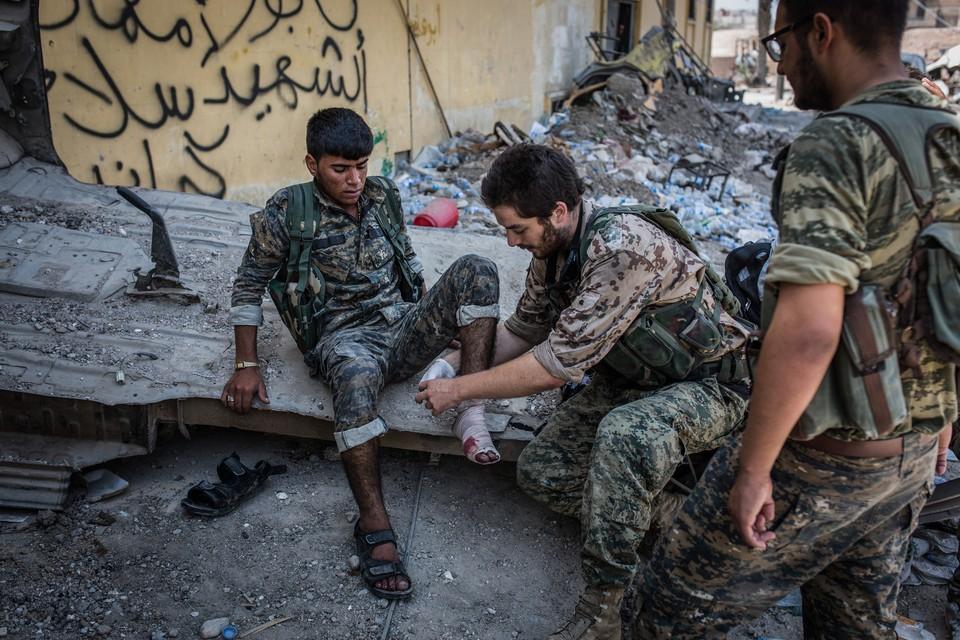 Бойцы СДС оказывают первую помощь раненному солдату в Ракке