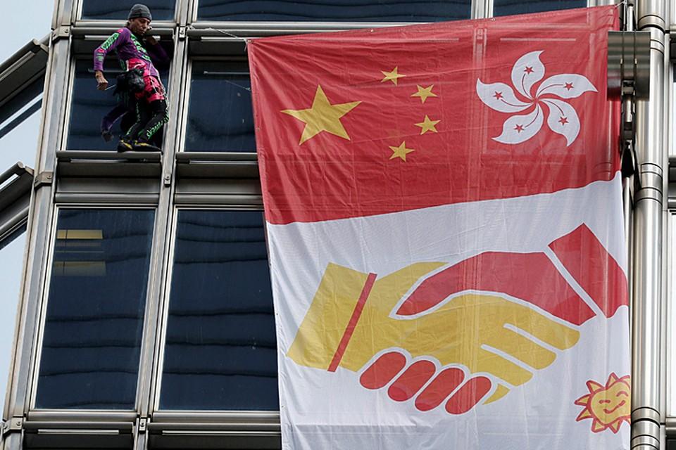 С собой экстремал прихватил плакат, в центре которого было изображено символичное рукопожатие двух стран Китая и Гонконга