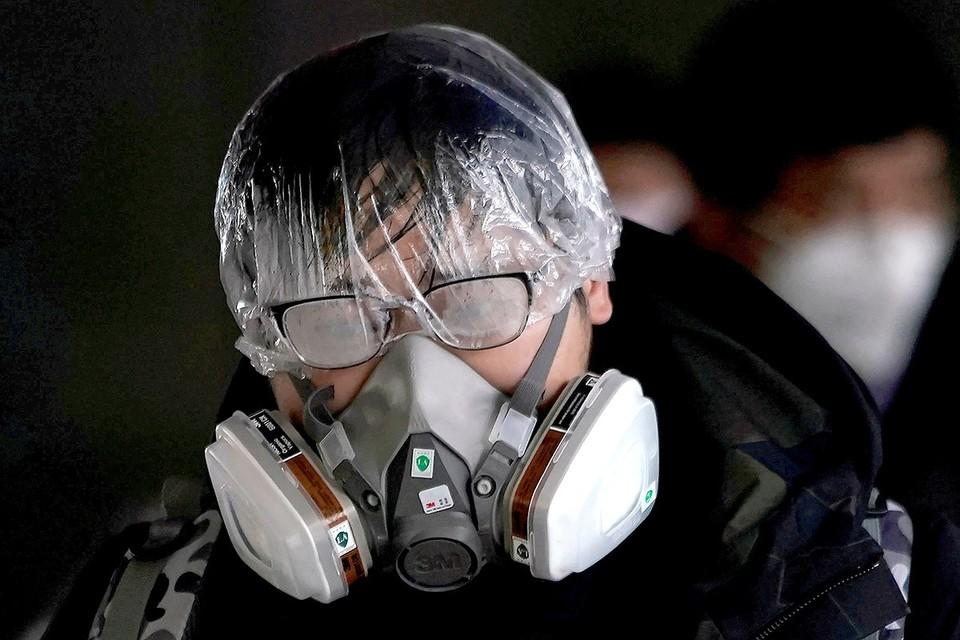 Пассажир метрополитена Шанхая в самодельной противовирусной защите.
