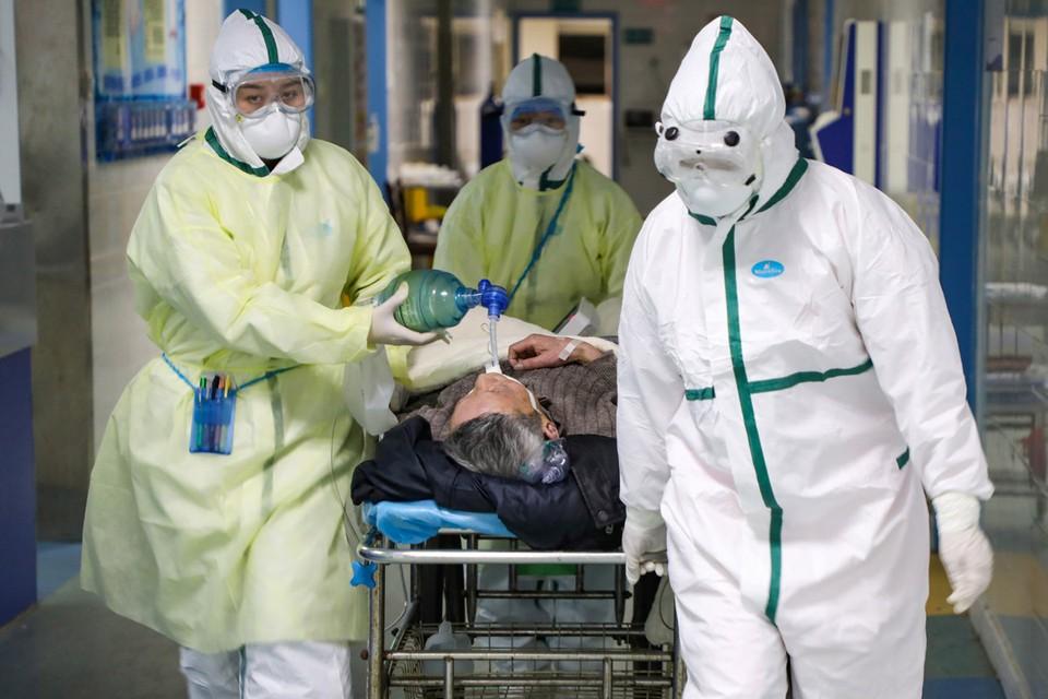 Медики и пациентка центра для лечения заразившихся коронавирусом в китайском городе Ухань.