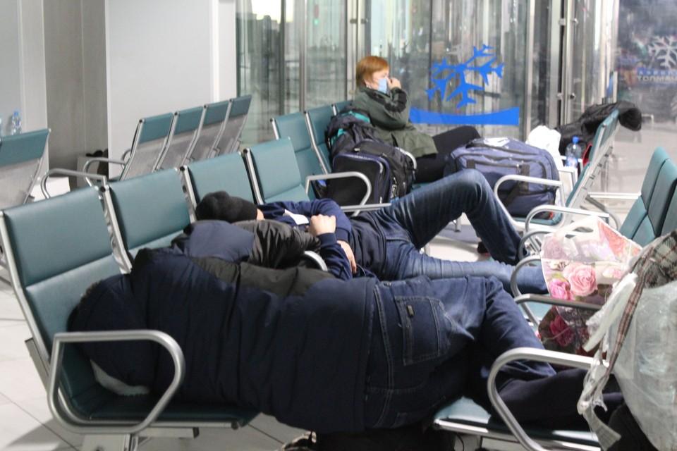 Иностранцы спят в зале ожидания.
