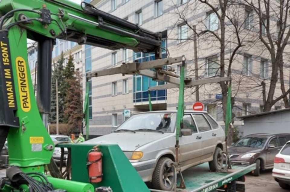 Эвакуаторы увозят автомобили с парковки.