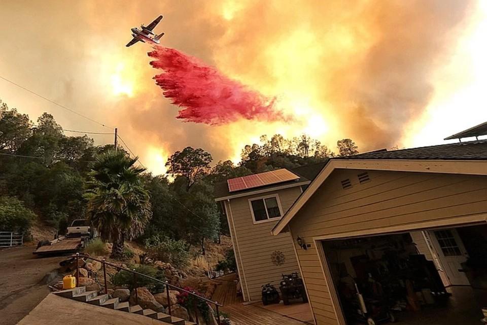 Пожарный самолет сбрасывает огнетушащий состав в Калифорнии, где лесные пожары угрожают жилым постройкам.
