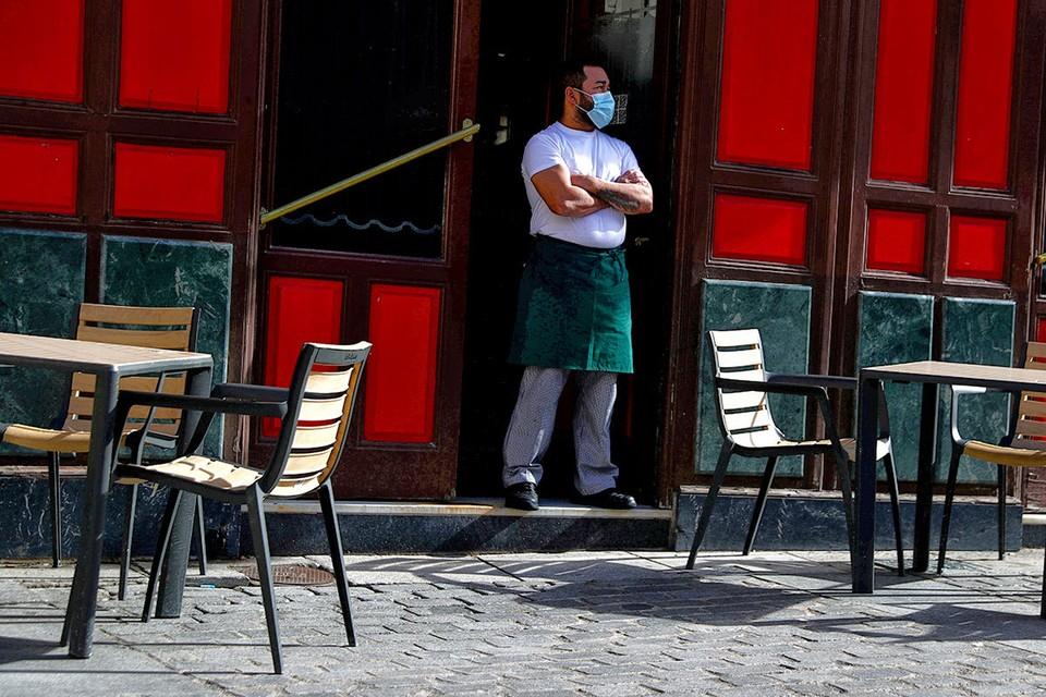 Официант ждёт гостей на пороге одного из кафе в Мадриде.