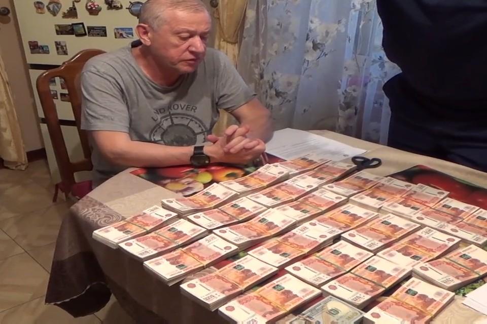 Евгений Тефтелев считает миллионы на кухонном столе Фото: скрин из видео УФСБ России по Челябинской области