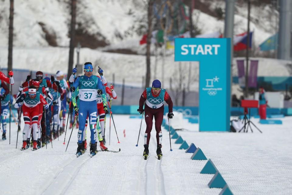 Олимпийский спортсмен из России Алексей Червоткин (справа) во время масс-старта на 50 км классическим стилем на соревнованиях по лыжным гонкам.