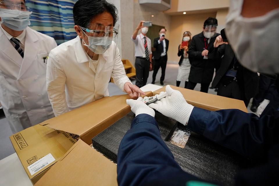 Япония. Персонал больницы тщательно проверяет температуру препарата от Pfizer перед началом вакцинации.