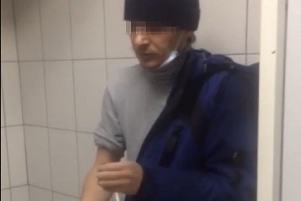 Новосибирцы сняли на видео наркомана, который принял дозу в туалете ТЦ. Фото: стоп-кадр.