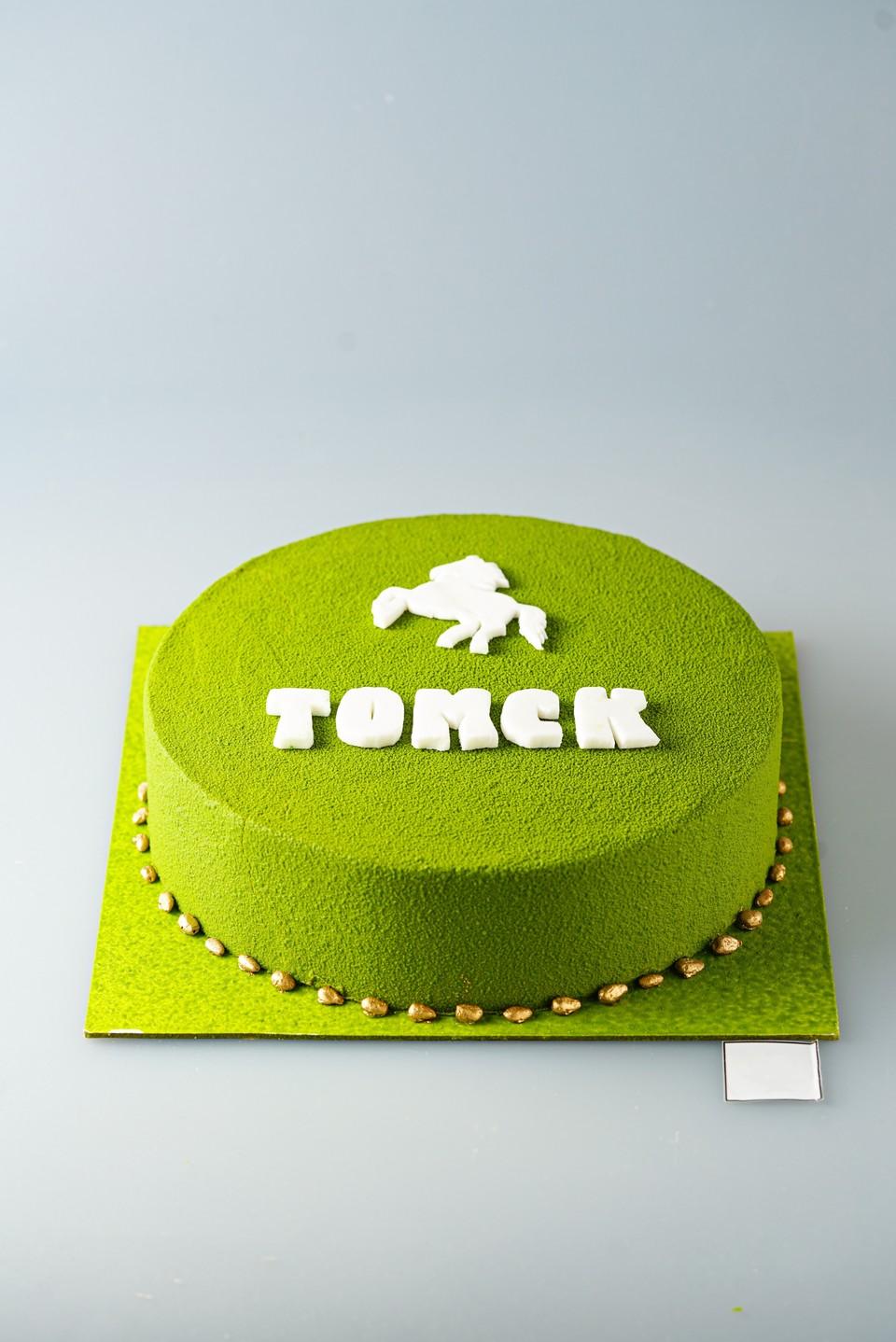 Оформление торта выполнено в технике велюр, в характерной для Томской области зеленой цветовой гамме, с нанесением названия и символа города. Нижний кант украшен кедровыми орешками.