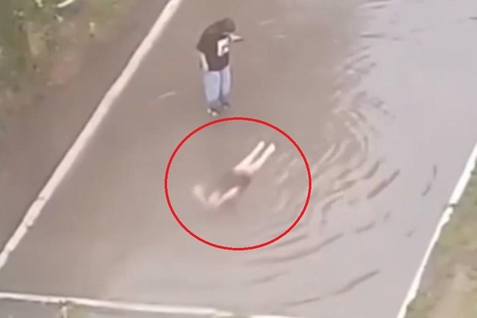 Женщина бесстрашно вымыла голову в грязной луже. Фото: скриншот