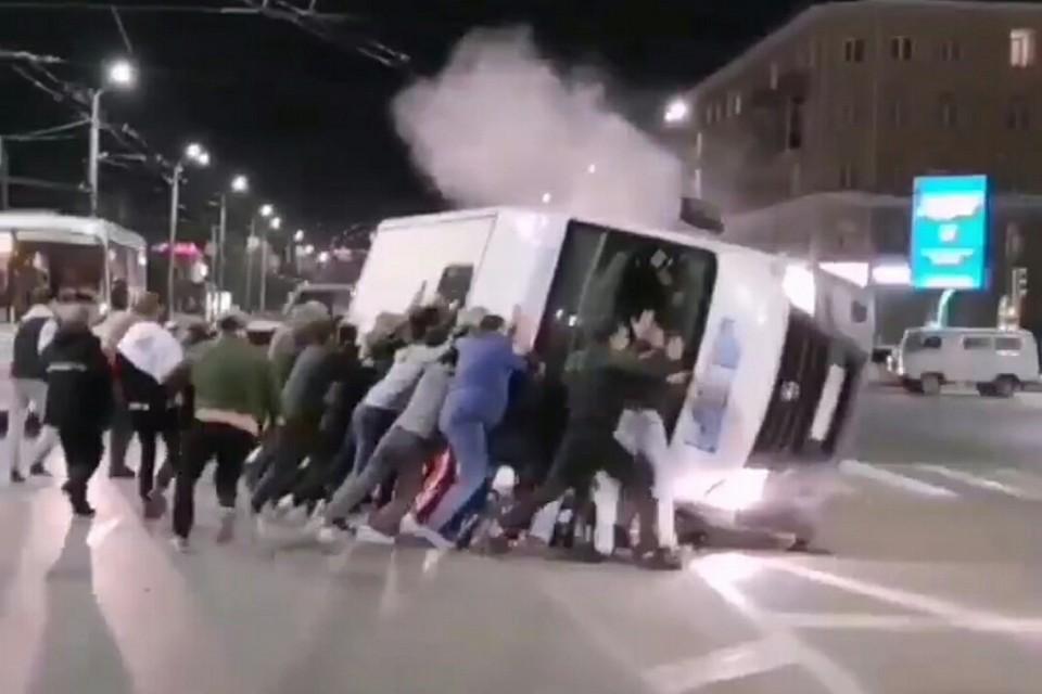 Очевидцы помогли поставить микроавтобус на колеса. Фото: скриншот видео («Омск Live»)