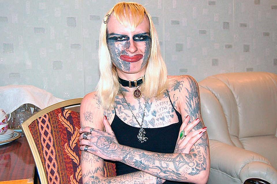 девушка в татуировках рядом со спортивными машинами