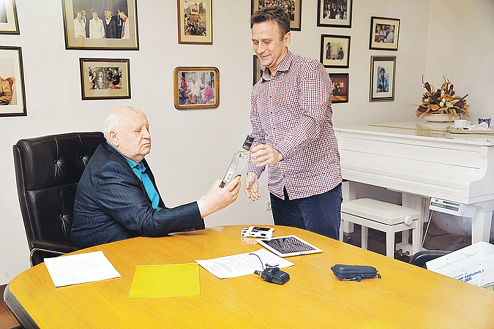 Михаил Горбачев с интересом рассматривает бутылку водки, подаренную в честь годовщины антиалкогольной кампании обозревателем «КП» Владимиром Ворсобиным.