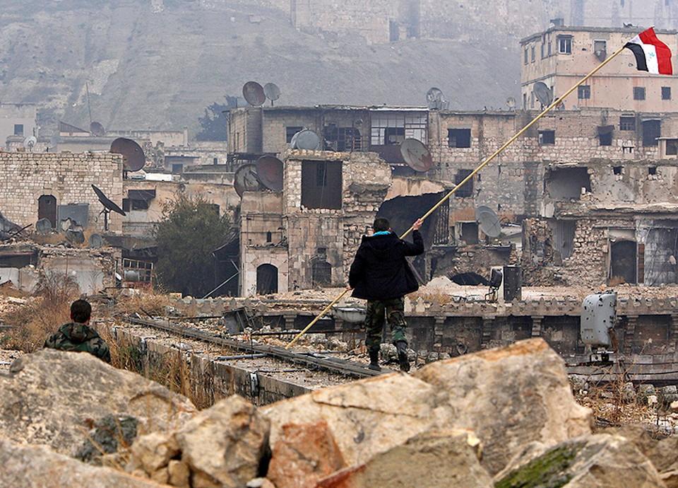 Сирийский солдат готовится установить флаг в освобожденном от бойцов оппозиции районе Алеппо.
