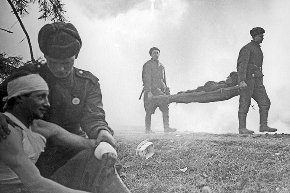 Советские санитары выносят раненых с поля боя. А. Новиков/ Фотохроника ТАСС