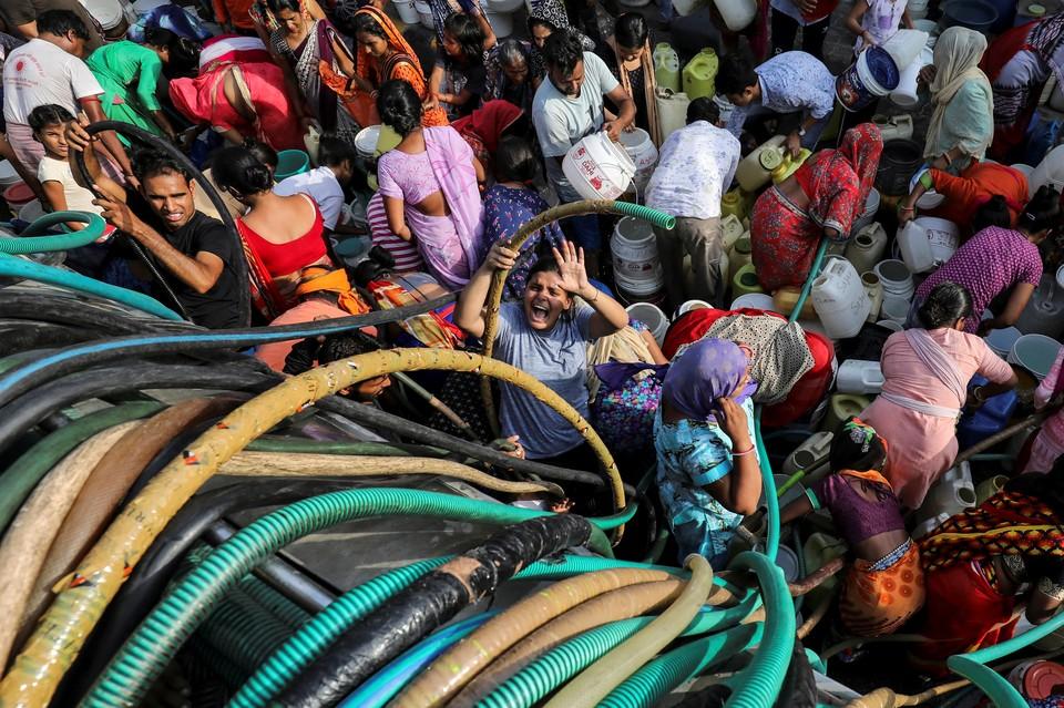 Жители одного из районов Дели наполняют свои емкости для воды у цистерны.