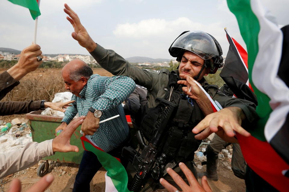Израильский полицейский отбивается от палестинцев во время протестов.