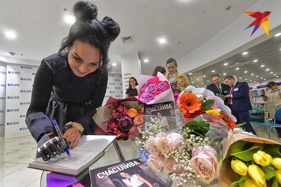 """Маргарита Грачева подписывает экземпляр своей книги """"Счастлива без рук"""" во время презентации в одном из московских ТЦ."""
