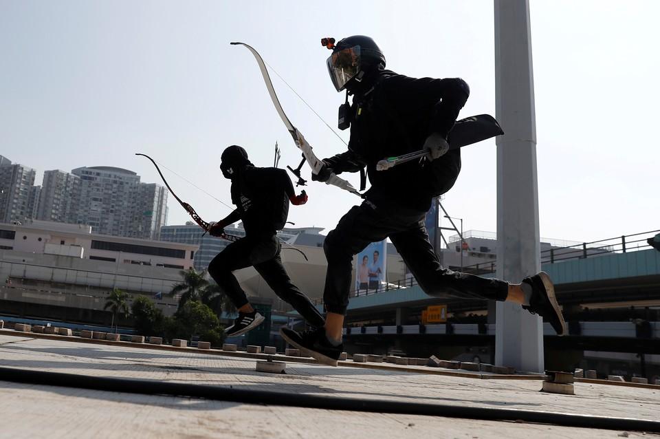 Вооруженные луками участники уличных протестов в Гонконге отрабатывают бегство от полицейских.