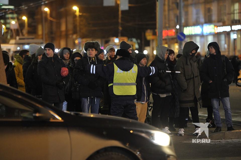 Сотрудник ДПС сдерживает толпу людей на перекрестке, во время проезда колонны машин генерального прокурора России Юрия Чайки