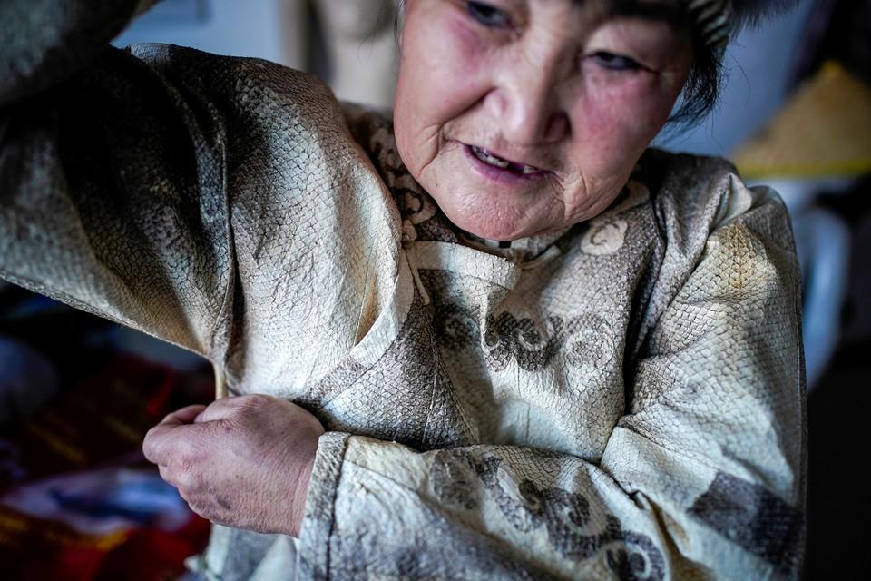 Китаянка Ю Вэнвэнь демонстрирует качества одежды, которую она изготавливает из рыбьей кожи.
