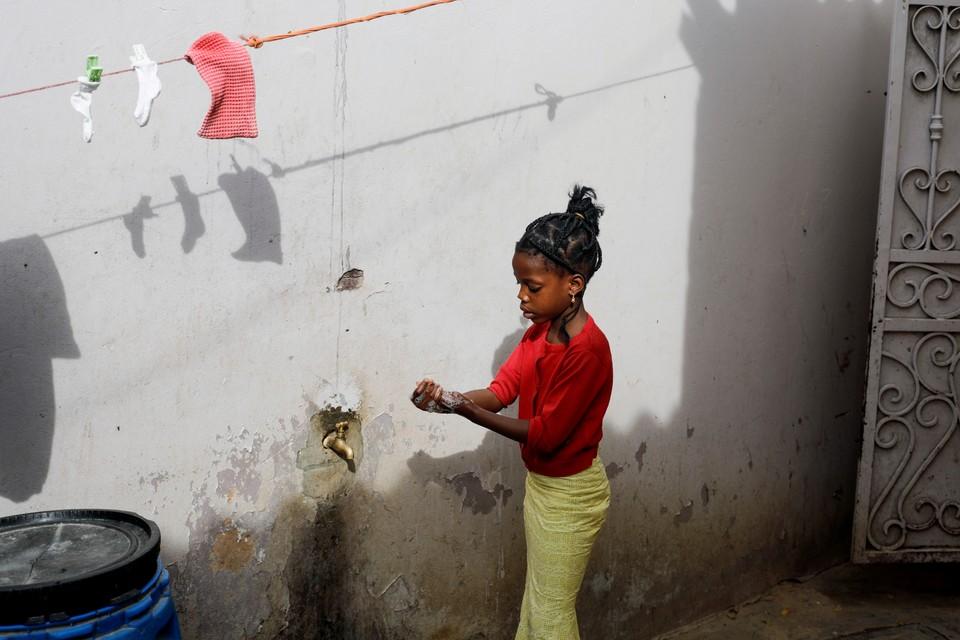 Сенегал, девочка тщательно моет руки с мылом во дворе своего дома.