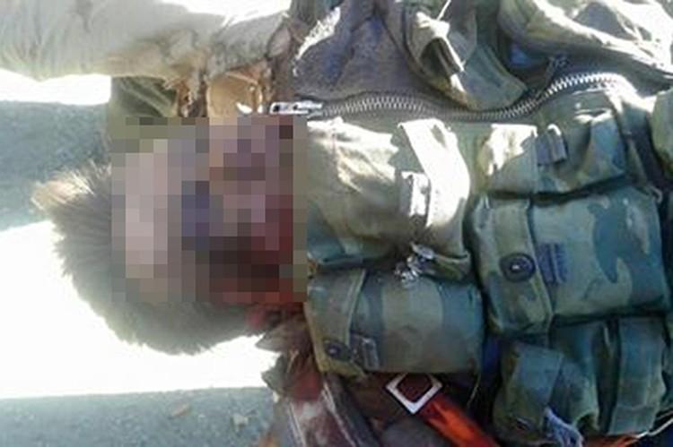 Вооруженные до зубов нелюди радостно позируют перед окровавленным телом российского офицера