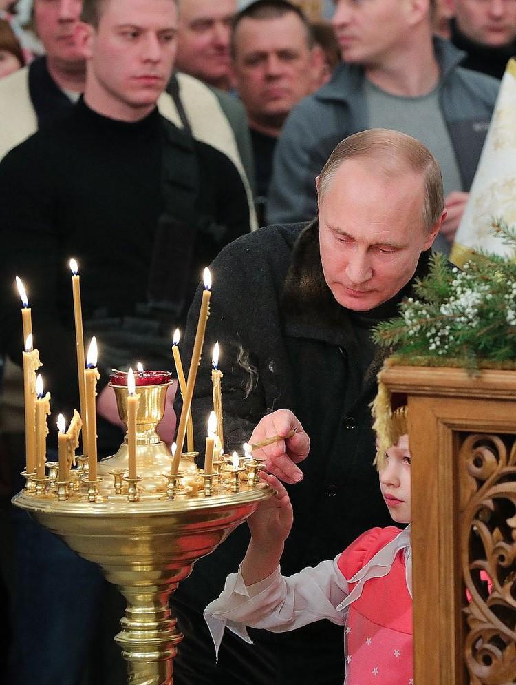 В храме Путин помог девочке поставить свечку. Фото: Михаил Климентьев/пресс-служба президента РФ/ТАСС