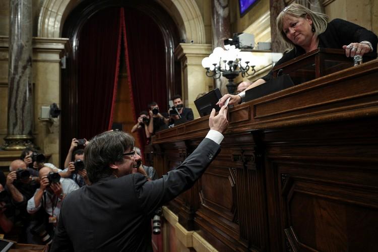 Президент Каталонии Карлес Пучдемон вручает свой биллютень предисдателю парламента в Барселоне.