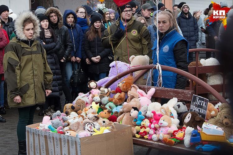 Кемеровчане несут цветы и мягкие игрушки к месту трагедии. Среди погибших в огне пожара - много детей.