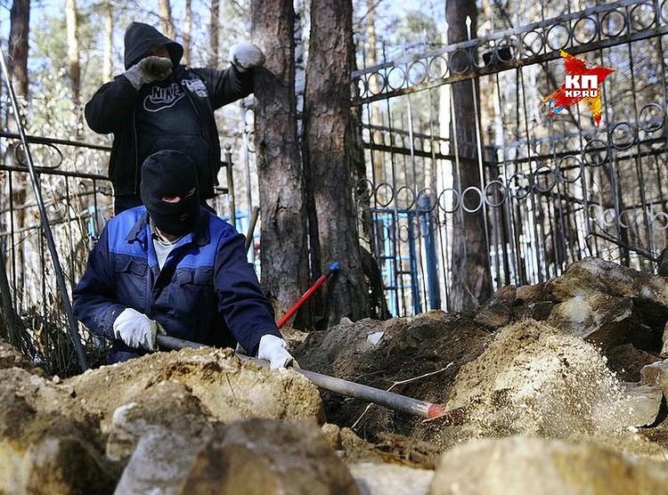 Рабочие вскрывают могилу.