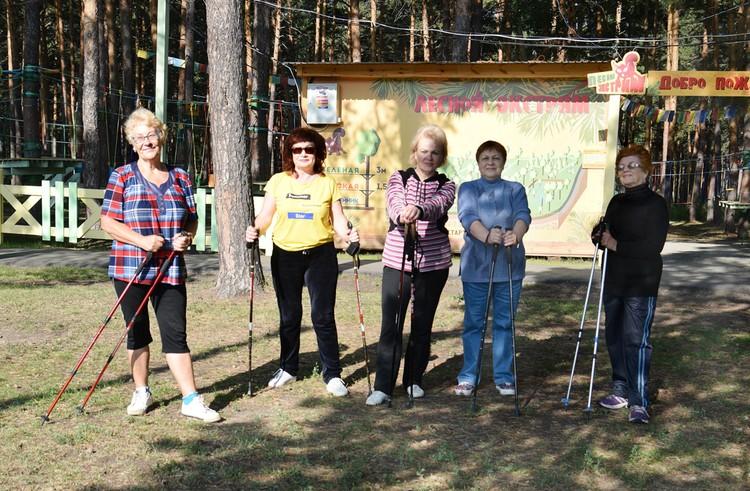 На тропинках пенсионерки занимаются скандинавской ходьбой.
