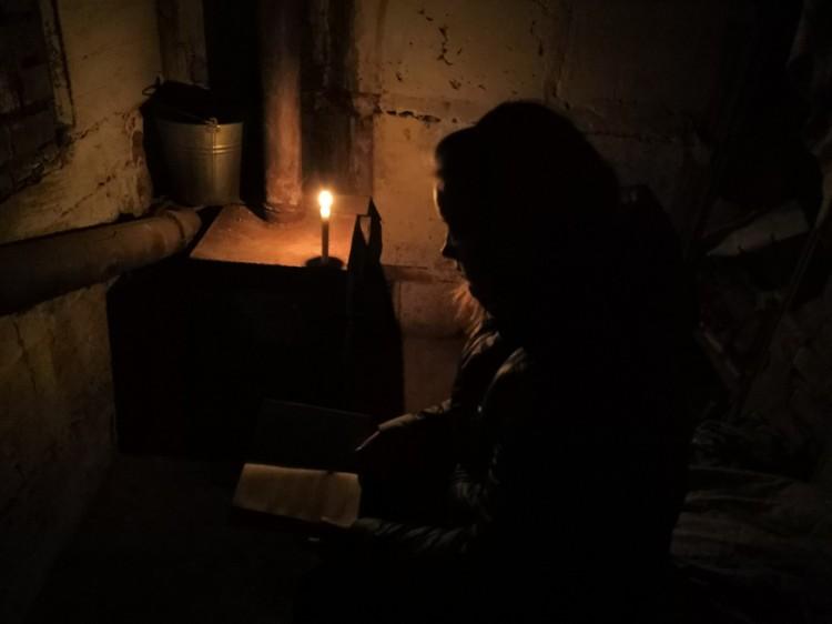 Вика в подвале делает уроки при свече.