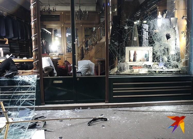Разбитая витрина ателье делового мужского костюма.