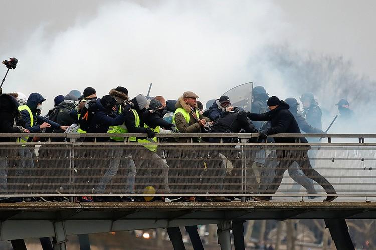 """Противостояние """"желтых жилетов"""" и полицейских на одном из пешеходных мостов Парижа."""
