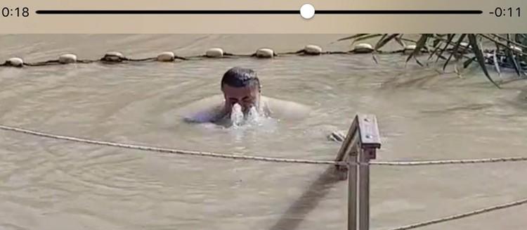 Вот он окунается в реку Иордан в день Великого Крещения