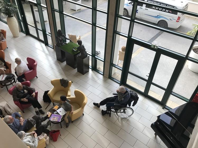 В холле клиники пациенты общаются друг с другом и своими семьями, слушают концерты, читают.