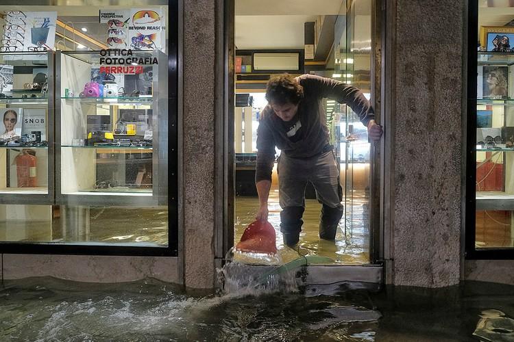Работник лавки оптики пытается спасти свой магазин от воды.